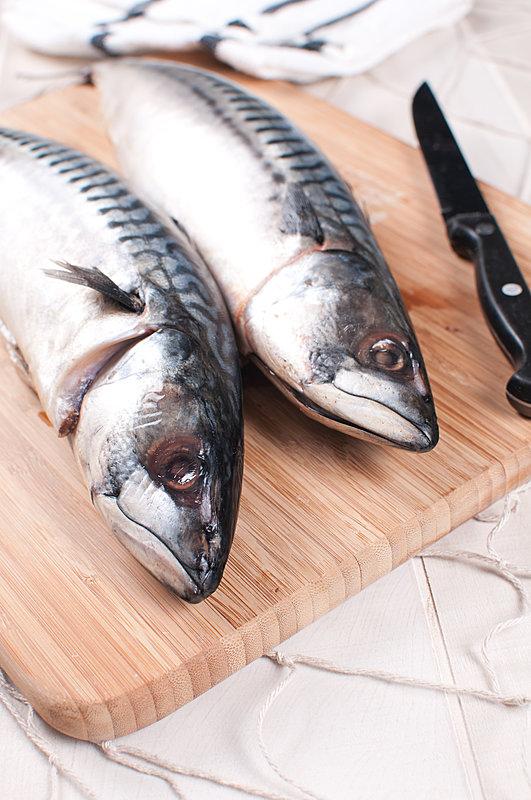 cooking raw mackerel fish on cutting board   marina food